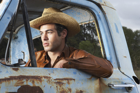 leaning on the truck: Man In Cowboy Hat and Rusty Truck