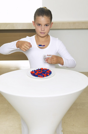 Portrait of Girl Sitting at Table Eating Meal of Pills LANG_EVOIMAGES