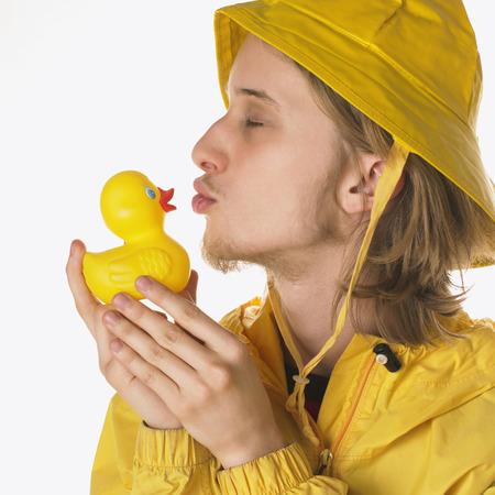 Teenager Wearing Raincoat, Kissing Rubber Duck LANG_EVOIMAGES