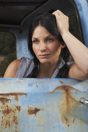leaning on the truck: Woman in Rusty Pickup Truck LANG_EVOIMAGES