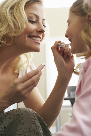 Mother Applying Lip Gloss on Daughter LANG_EVOIMAGES