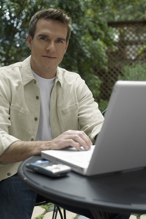 homeoffice: Man Sitting Outside With Laptop Computer