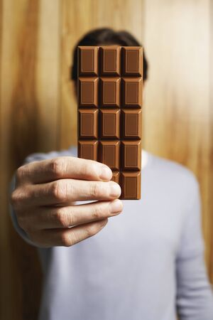Man Covering Face with Bar of Chocolate