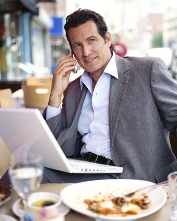 run down: Businessman at Restaurant with Laptop Computer and Cellular Phone