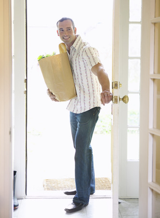 Man Entering Home with Groceries