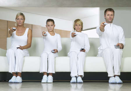 Portrait of Family Sitting on Sofa, Using Remote Controls LANG_EVOIMAGES