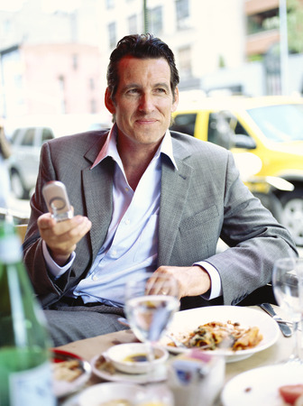 run down: Businessman at Restaurant with Cellular Phone LANG_EVOIMAGES