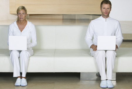 Portrait of Couple Sitting on sofa, Using Laptops LANG_EVOIMAGES