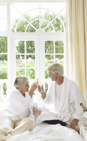 Mature Couple Drinking Champagne In Bed