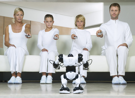 Portrait of Family Sitting on Sofa, Using Remote Controls on Robot
