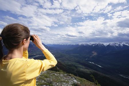30 years old man: Woman Looking at Canadian Rockies Through Binoculars