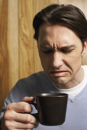 wood panelled: Man Making Face at Bitter Cup of Coffee