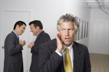 skepticism: Businessman Listening to Colleagues Gossiping in Hallway