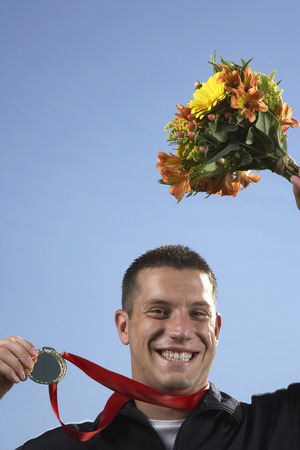 Man Holding Medal and Bouquet