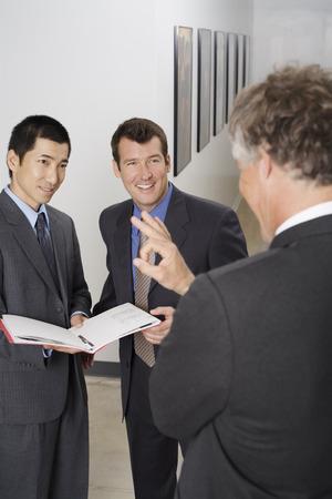 goodluck: Businessmen Talking in Office Hallway LANG_EVOIMAGES