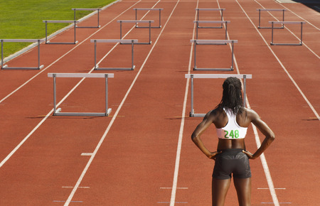 Back View of Woman Standing in Front of Hurdles on Track