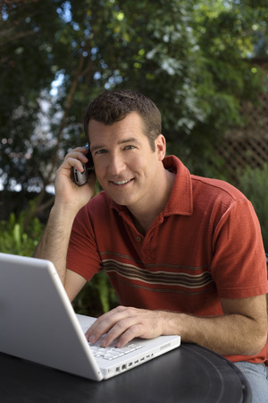 Man in Backyard using Cell Phone and Computer LANG_EVOIMAGES