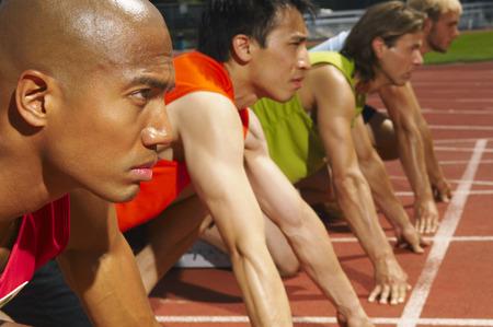athletic wear: Men Lined up at Starting Blocks