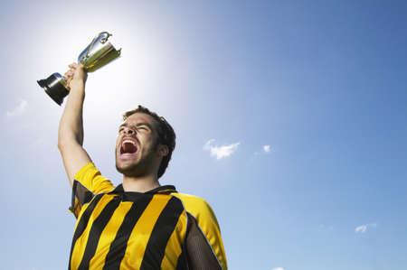 egoistic: Portrait of Soccer Player Holding Trophy LANG_EVOIMAGES