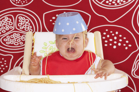 Baby in High Chair with Spaghetti Bowl on Head