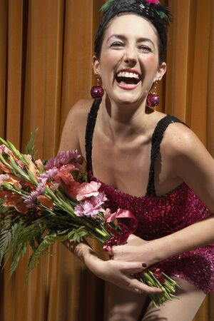 Woman on Stage Holding Flowers LANG_EVOIMAGES