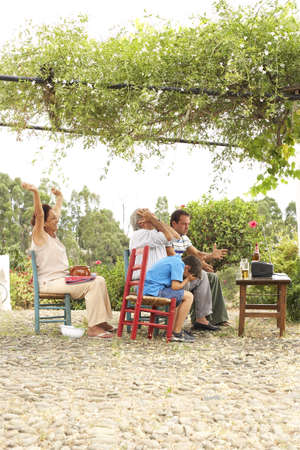 long bean: Grandfather, Grandmother, Father and Son Watching Television in Backyard