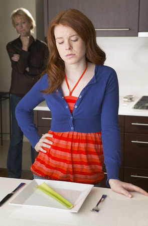 disapprove: Mother Looking at Daughter in Kitchen with Celery