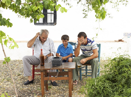 front desk: Grandfather, Father and Son Watching Television in Backyard LANG_EVOIMAGES