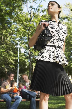 leer: Woman Standing in Front of Men with Babies in Park LANG_EVOIMAGES