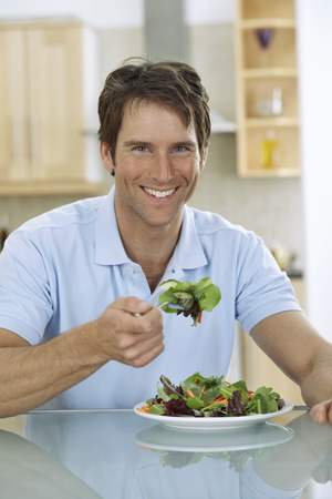 counter top: Man Eating Salad
