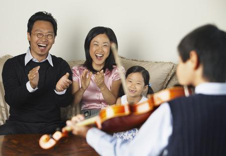family sofa: Family Watching Boy Play Violin