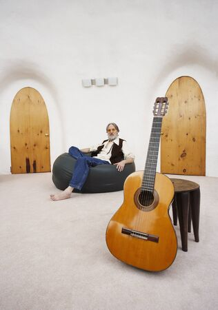 Man Sitting in Bean Bag Chair with Guitar in Foreground