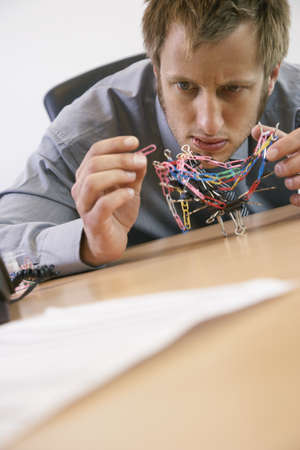 front desk: Businessman Playing with Paperclips