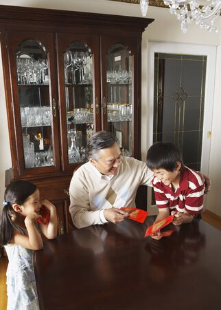 goodluck: Grandfather with Grandchildren Holding Ang Pow Envelopes LANG_EVOIMAGES