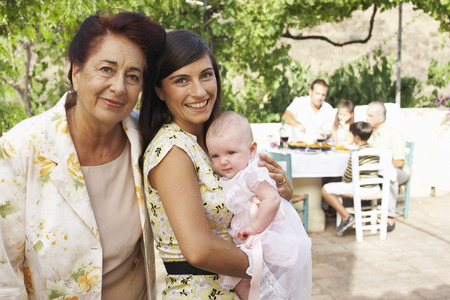 three generation: Portrait of Grandmother, Mother and Baby, with other Family Members in Background