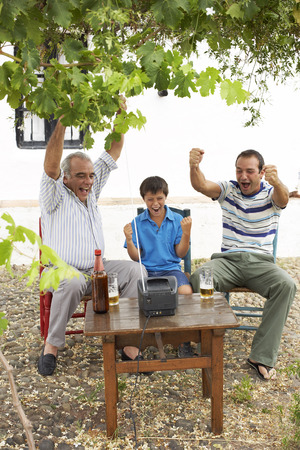 three generation: Grandfather, Father and Son Watching Television in Backyard LANG_EVOIMAGES