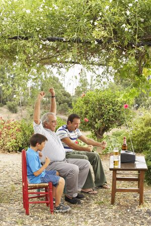 grampa: Grandfather, Father and Son Watching Television in Backyard LANG_EVOIMAGES