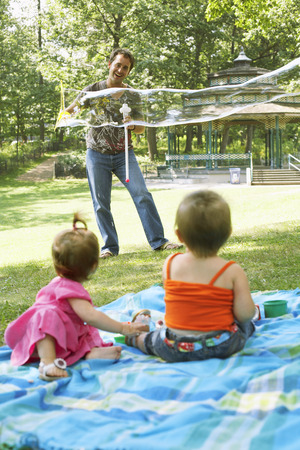sitting on the ground: Father Blowing Bubbles while Babies Watch LANG_EVOIMAGES