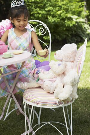 front desk: Girl Serving Tea at Tea Party LANG_EVOIMAGES