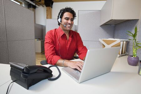 Businessman with Headset and Laptop Computer LANG_EVOIMAGES