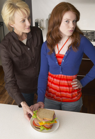 Mother Looking at Daughter in Kitchen with Sandwich