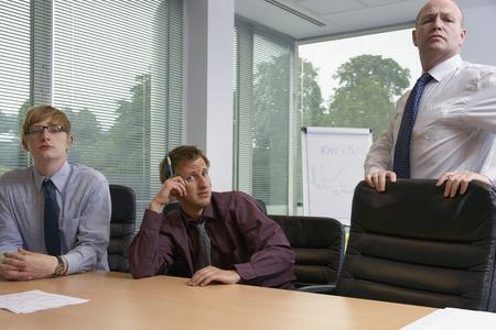 skepticism: Manager and Staff in Boardroom Office LANG_EVOIMAGES