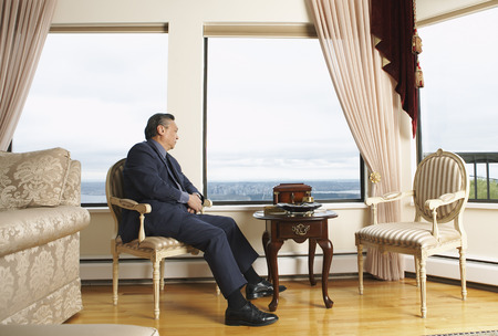 luxurious: Man Sitting by Window in Elegant Home