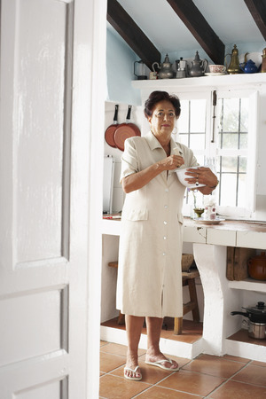 Woman with Mixing Bowl in Kitchen