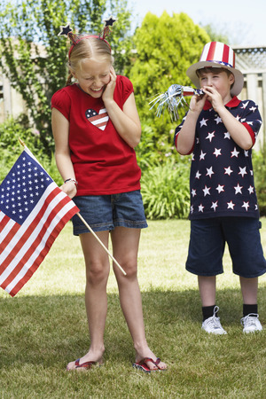 Girl Holding American Flag with Boy Wearing Stars and Stripes Top and Hat, Blowing Noisemaker Horn LANG_EVOIMAGES