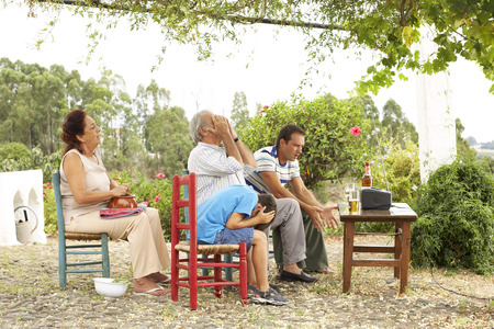 Grandfather, Grandmother, Father and Son Watching Television in Backyard