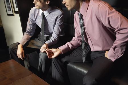societal: Businessmen Exchanging Microchip LANG_EVOIMAGES