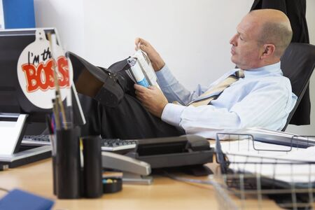 egoistic: Boss Reading Magazine at Desk LANG_EVOIMAGES