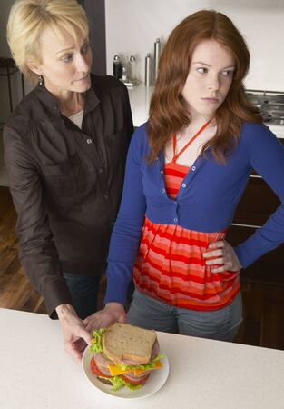 disapprove: Mother Looking at Daughter in Kitchen with Sandwich
