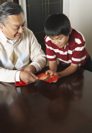 goodluck: Grandfather and Grandson Holding Ang Pow Envelopes